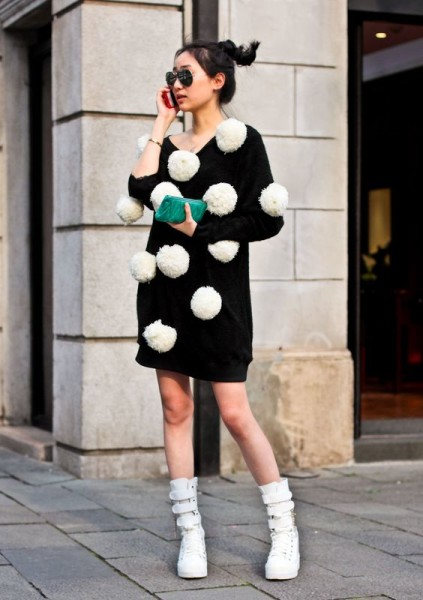 a black knit covered in cute white pom poms, teamed with a bright green clutch.