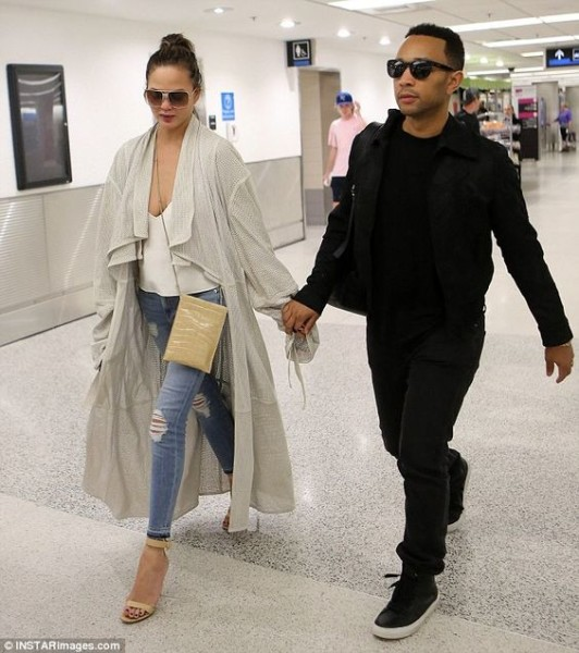 Chrissy Teigen and John Legend hold hands after jetting into Miami