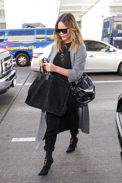 Chrissy Teigen accessorized with a Givenchy Mini Nightingale along with an Aerin suede weekend bag.