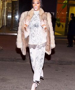 Winnie Harlow in floral ensemble and furry jacket.
