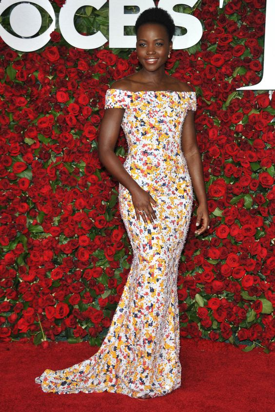 Lupita Nyong'o shows how off the shoulder is done for evening in a fitted floral by Boss