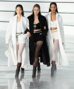 Gigi Hadid rocked a black tweed coat, crop-top, and hot pants combo at the Chanel Fall 2020 runway show.